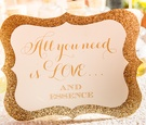 "Wedding shower perfume station with a gold glitter sign, ""All you need is love...and Essence"""