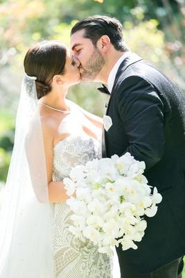 bride in leah da gloria gown, bedazzled veil, orchid bouquet, kisses groom