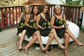 Four bridesmaids on ottoman in brown short dresses and matching bouquets