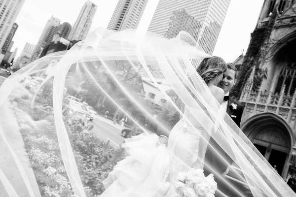 Black and white photo bride Vera Wang wedding dress and veil with husband on wedding day in Chicago