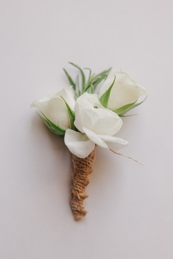 White rose boutonniere tied with burlap