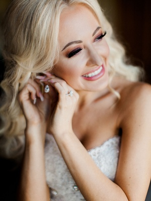 Bride in smokey eye makeup with pink lipstick blonde hair putting on diamond earring before wedding