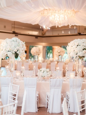 Drapery and chandelier over dance floor blush linens white flower centerpieces and chair covers