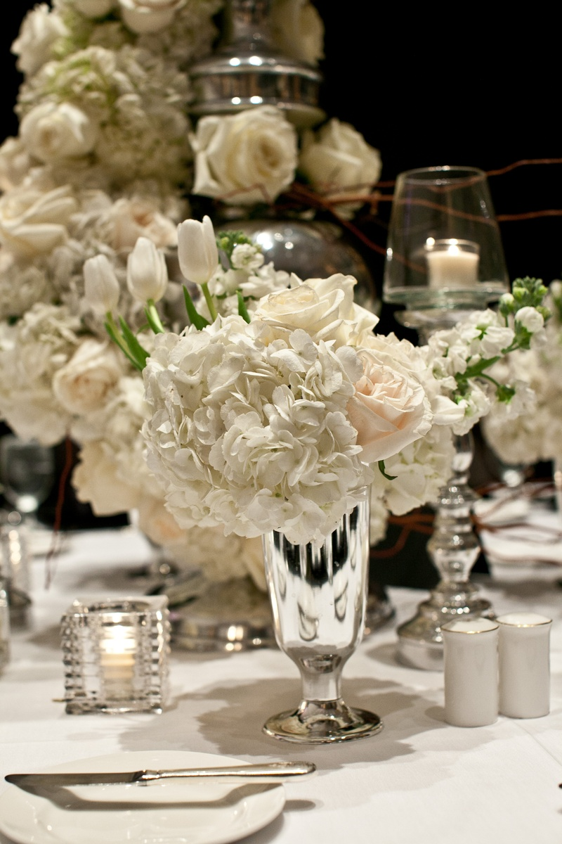 White reception table with small centerpiece in silver vase