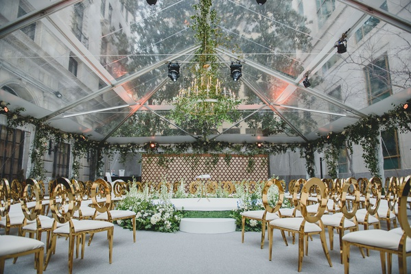 wedding ceremony open tent area greenery flower chandelier gold oval back chairs stage greenery