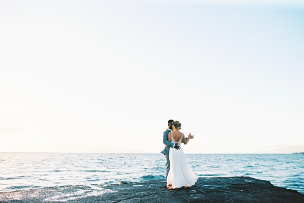 bride in lihi hod, groom in grey suit, maui wedding, dancing on the rocks by the ocean