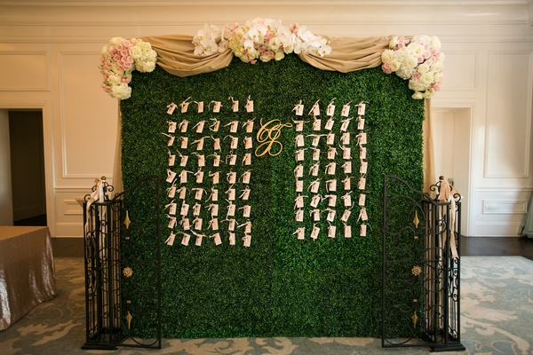 boxwood wall to display escort cards, drapery with flowers along the top