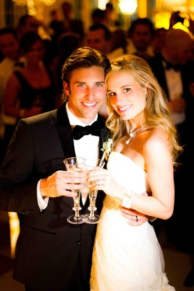 Tuxedo groom and strapless bride dress with champagne flutes