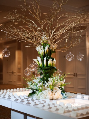 Wedding reception white table with large arrangement of greenery, white flowers calla lily branches