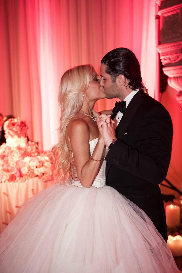Bride and groom kiss at pink wedding reception