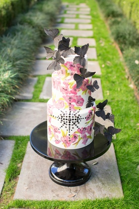 white cake with pink flower design and black jewels and black butterflies on top on stone path