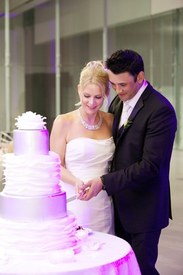 Bride and groom cutting white and silver ruffle cake