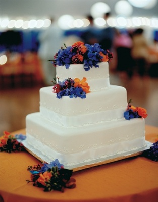 White cake with blue and orange fresh flower topper