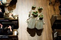 Aerial bird's eye view of flower girls four walking down wood floor aisle church wedding ceremony