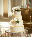 Four layer wedding cake on silver cake stand white rose green leaves swiss dot gold border tiers