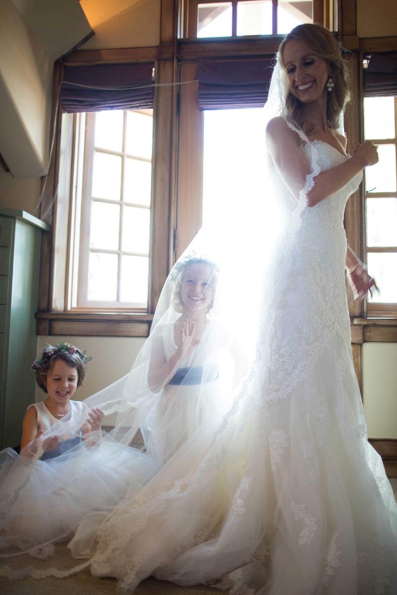 flower girls play under brides veil bride smiling flower crowns sash dresses