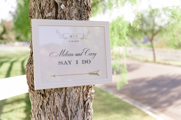 Directional sign with the couple's names, initials, and arrow for outdoor ceremony posted on tree