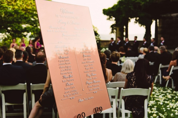 Welcome sign list of attendants and wedding party at entrance to outdoor ceremony