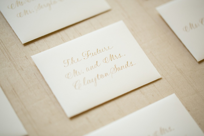 White stationery seating cards with handwritten gold names