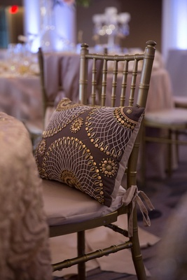 Wedding reception with chocolate throw pillow with beaded pattern on gold chiavari chair