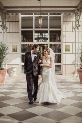 Bride in strapless mermaid wedding dress sweetheart neckline groom in suit and bow tie checker floor