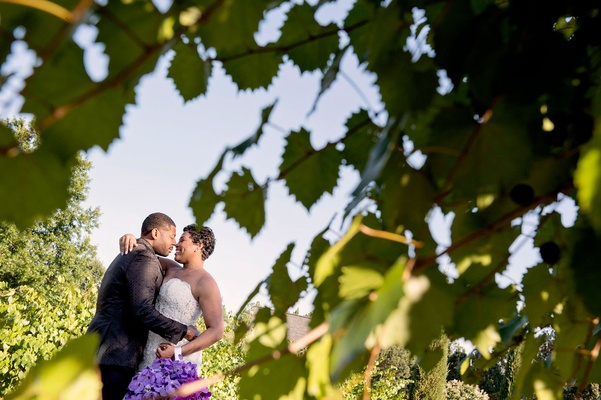 Bride in strapless wedding dress hugging groom portrait through leaves artistic wedding photo purple