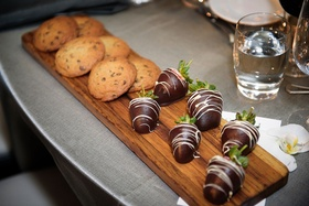 Wedding dessert wood cutting board with chocolate chip cookie desserts and chocolate dipped berries