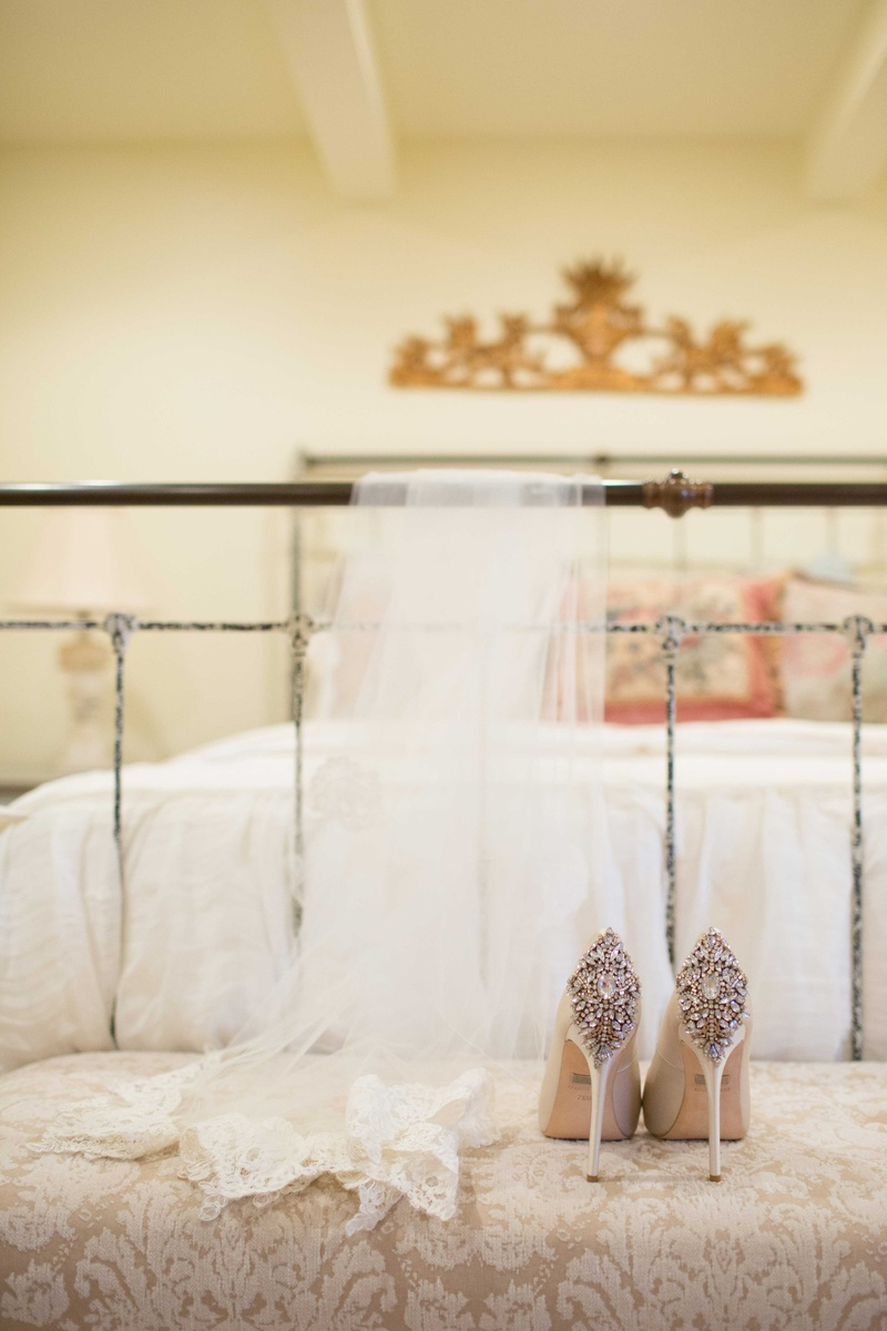 white bridal veil and white tan champagne high heel shoes on cushion near white bed
