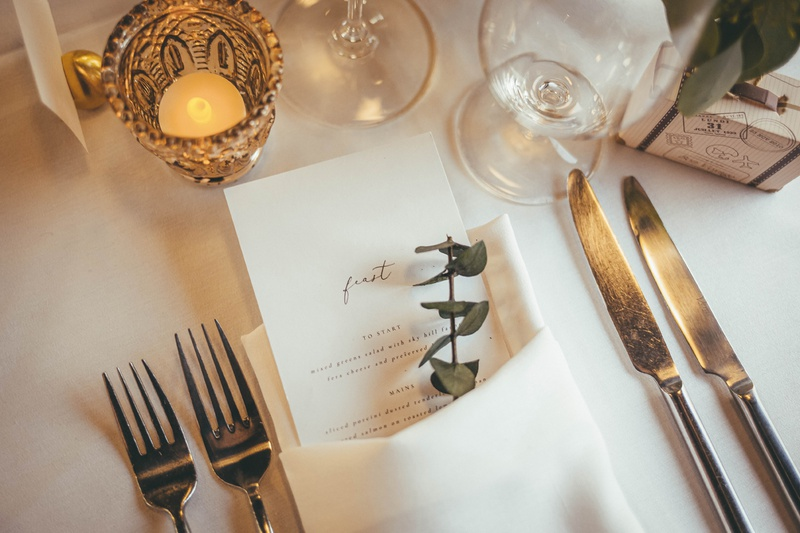 """wedding menu that says """"feast"""" paired with sprig of eucalyptus"""