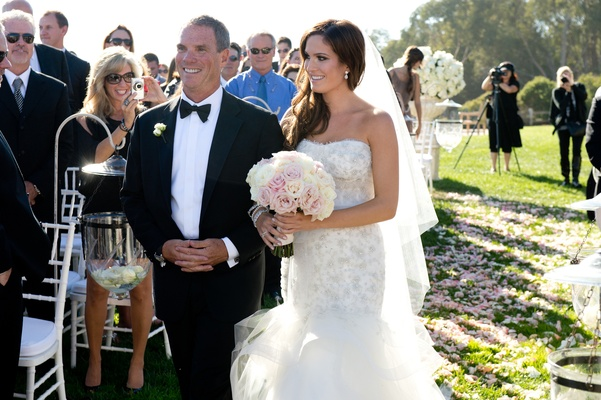 Bride and father of bride walk down pink petal aisleway