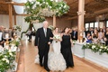 wedding ceremony processional bride walking down aisle with mother and father who also officiated