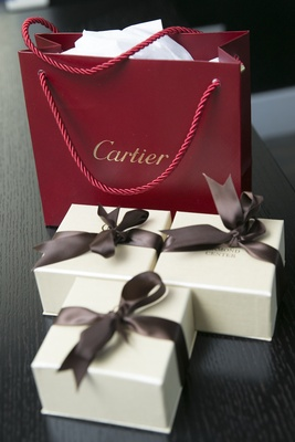 Red Cartier bag three ivory boxes with brown ribbon bows at wedding