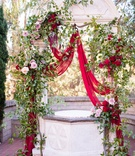 ceremony altar with scarlet drapery, roses, greenery