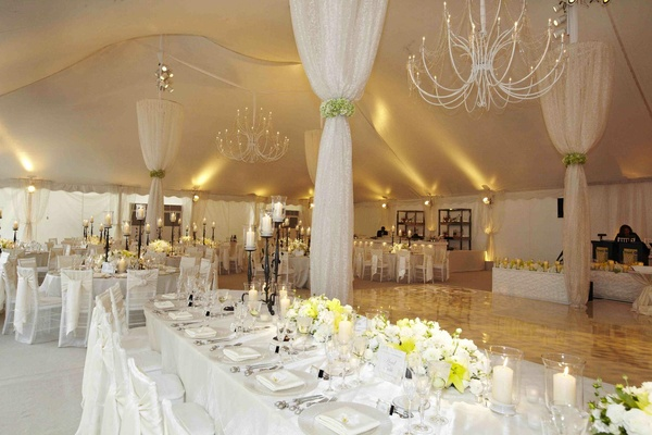 Tent wedding with white table decorations and drapery