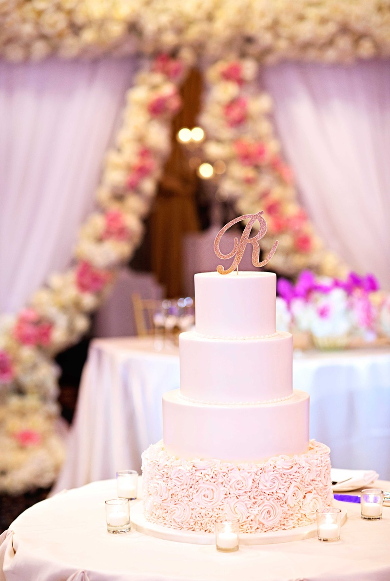four-tier wedding cake with rose frosted details on base, glitter gold monogram cake topper