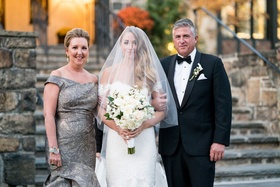 Bride in anne barge wedding dress off shoulder with father of bride tuxedo and mother in grey gown