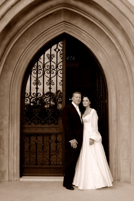 couple stands in front of dramatic arched doorway