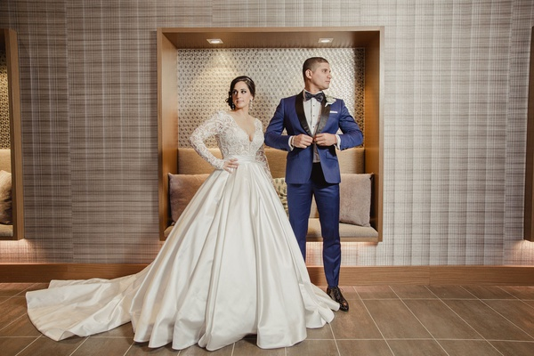 Bride in long sleeve pnina tornai ball gown wedding dress groom in navy tuxedo bow tie pose portrait