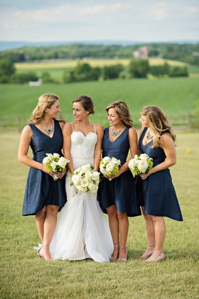 0f4016cc088 Bride in a Berta Bridal gown with bridesmaids in sleeveless navy dresses