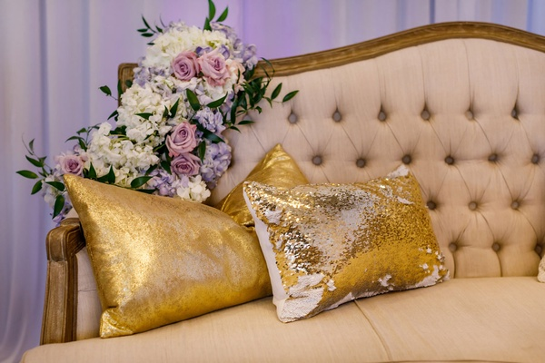 Wedding reception lounge tufted settee purple white flowers greenery gold pillows