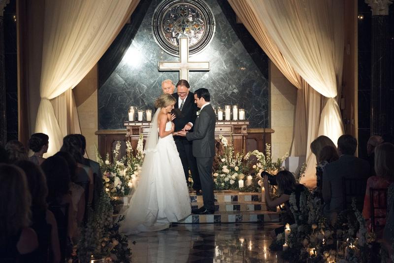 Bride and groom at church decor ceremony look cross candles low flower arrangement oscar de la renta