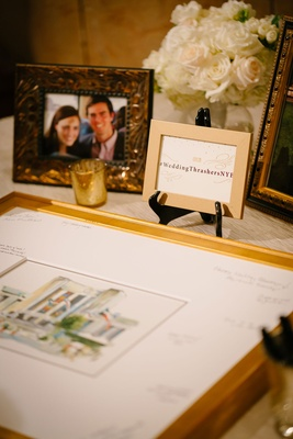 Wedding hashtag and gold framed photo with signatures in mat picture frame of couple at reception
