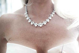 Bride wearing pearl necklace with diamond details