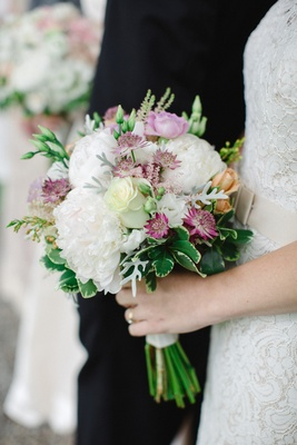 bridesmaids bouquet with white peonies, purple blossoms, and greenery