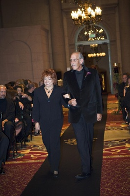Lady in a black pant suit is escorted down the aisle by a gentleman in a black velvet blazer