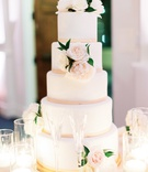 five-tier wedding cake with smooth frosting, blush border, fresh flowers