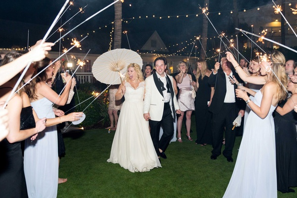 Bride holding white parasol with groom for night sparkler exit twinkle lights in sky