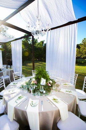 a round tablescape champagne colored linens overflowing foliage floral arrangement chandelier