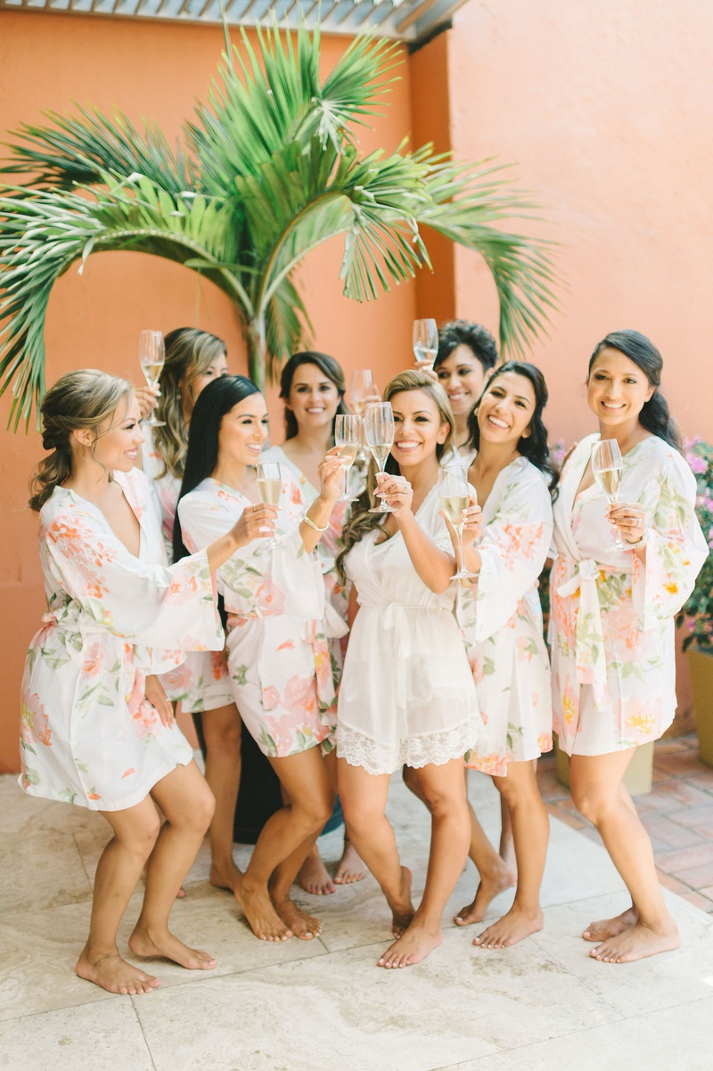 wedding party bridesmaids in pale peach flower print robes bride in white lace robe romper champagne