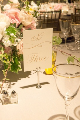 white and gold calligraphy number number on white table linens
